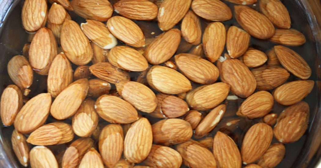 Add your almonds to a large bowl and cover completely with water